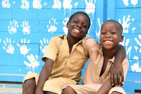Two children in Côte d'Ivoire wrap their arms around each other's shoulders, smiling outside their school playground.