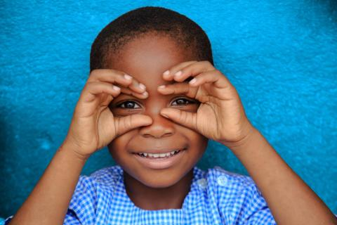 A young boy dressed in blue smiles outside a preschool in Côte d'Ivoire, in 2019.
