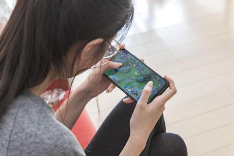 China. A girl plays a video game.