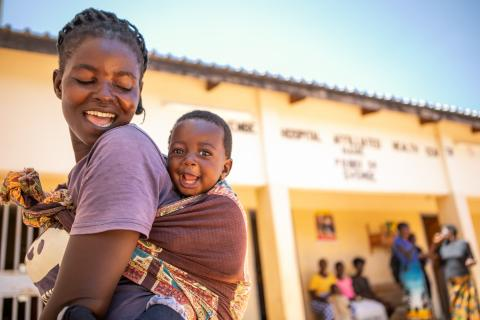 A smiling mother in Zambia holds her 10-month-old son on her back in 2020.