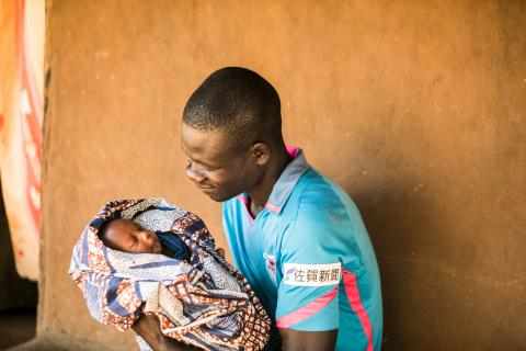A father holds his swaddled infant in Uganda in 2019.