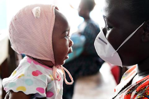 In April 2020, a mother in Côte d'Ivoire wears a mask to protect herself and her baby, whom she holds in front of her, from coronavirus disease (COVID-19).