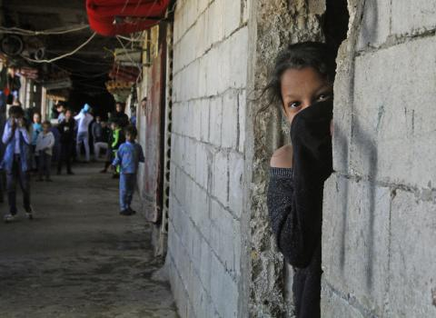 Lebanon. A Syrian refugee looks out of a doorway.