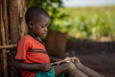 Malawi. A boy sits outside reading a book.