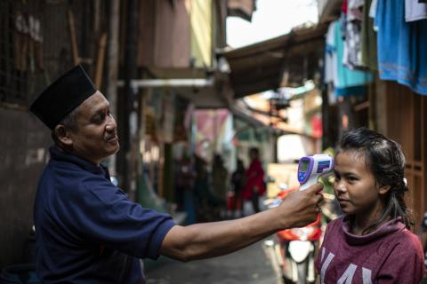 A man in Indonesia stands arm's-length away as he takes the temperature of a young girl during the COVID-19 pandemic in April 2020.