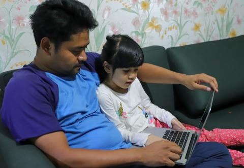A young girl studies at home with her father in Indonesia, 2020.