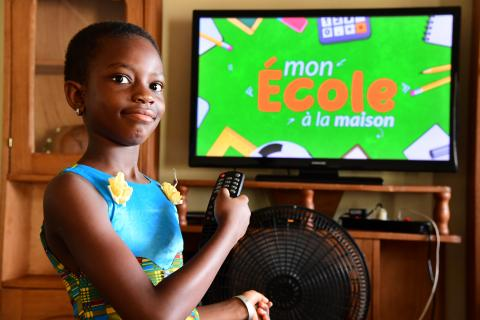 Côte d'Ivoire. A girl points at a TV screen.