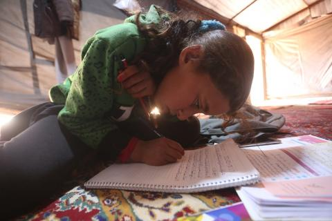 Syria. A girl does her homework.