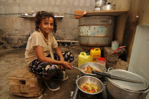 Yemen. A girl cooks in her family's kitchen.