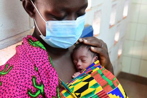 Mother in a protective masks holds a newborn baby.