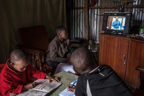 "12-year-old Elizabeth and 10-year-old Justin follow a Social Studies lesson on the EDU TV while doing their revision at home in Kibera. Justin's brother, Morara who is in the kindergarten doodles on an exercise book. Elizabeth is in Standard 6 and Justin is in Standard 5, ""I am familiar with most of the topics the teacher is teaching"" he said."