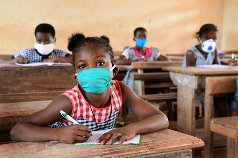 Côte d'Ivoire. A girl wearing a face mask sits in a classroom.
