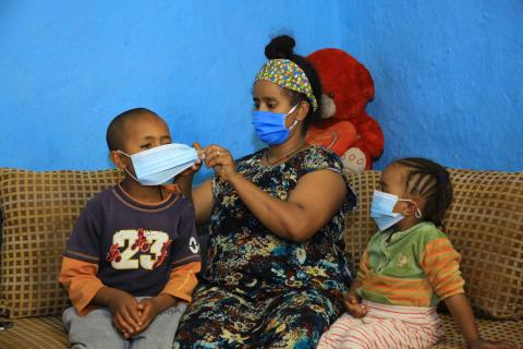 Adanech Tadesse, mother, is putting masks on her son face.