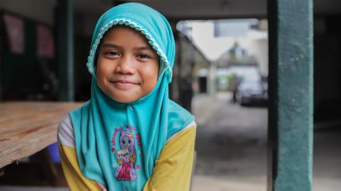 Mental health in Indonesia: A girl in traditional headgear smiles