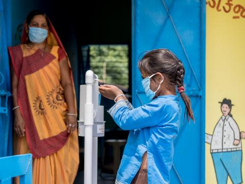 Six-year-old Payal in India uses a foot pedal sanitizer to practice hand hygiene.