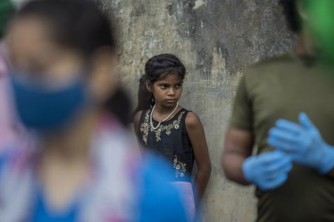 India. A girl watches other villagers receive a ration kit.