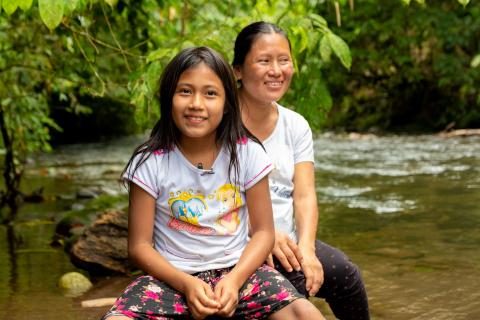 Ecuador. A girl sits with her mother near a river.