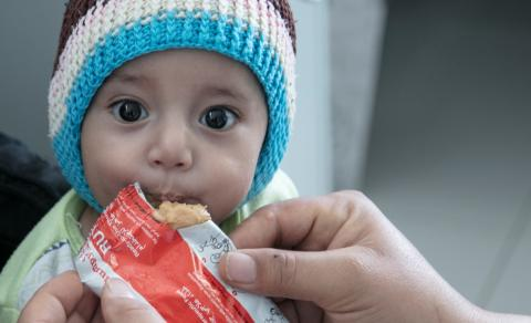 Yemen. A small child is fed a nutrition bar.