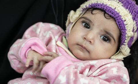 Yemen. A woman holds a small child.