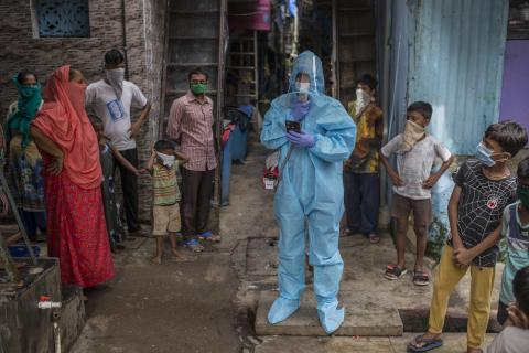 A coordinator for the COVID-19 awareness programme wearing PPE (Personal protective equipment) spreading awareness to take precaution as community members listen in Mumbai, India.