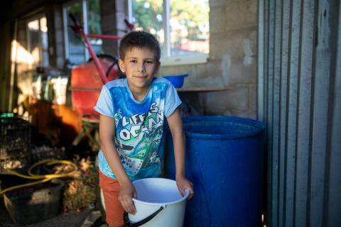 Ukraine. A  boy stands with a bucket of water.