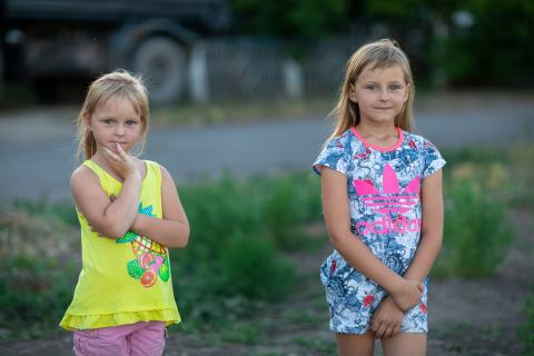 Ukraine. Two children stand near their home.