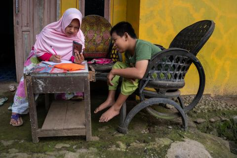 A child with a physical impairment, studies at home with his mother  in Banyumas, Indonesia.