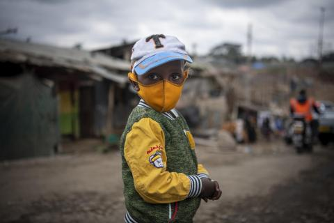 Kenya. A young boy wears a mask.