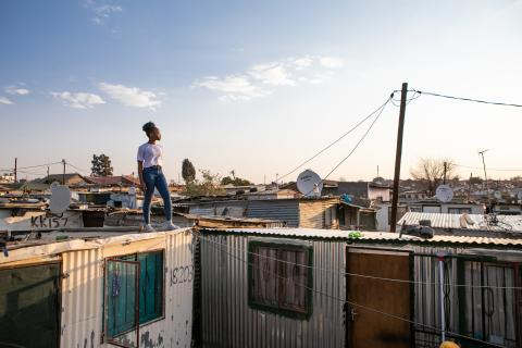 A teen girl stands on the corrugated roof of her home in Ivory Park, South Africa.