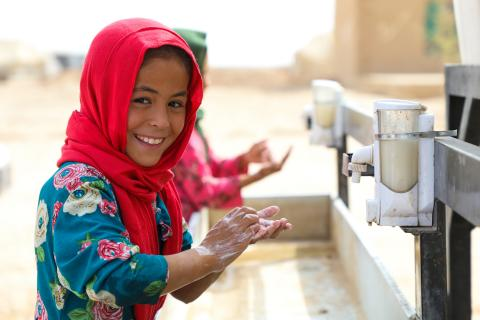 Somaya, 9, washes her hands in the Ferdousi camp, Nahri Shahi district of the Balkh province of Afghansitan.