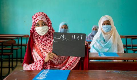 "The young Fatimetou carries her slate with the inscription ""I love school"" written on it in arabic in front of her classmates."