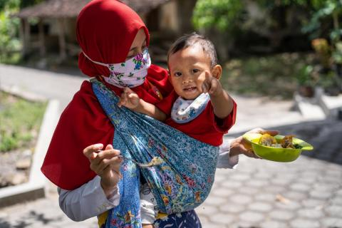A woman in Indonesia feeds her one-year-old son during the COVID-19 pandemic in 2020.
