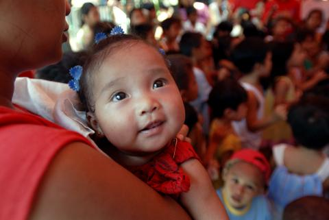 A baby is carried in the Philippines