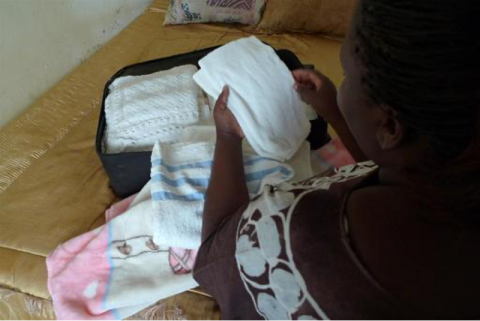 Zambia. Following the stillbirth of her baby, a woman unpacks the baby clothes and blankets she had prepared for her newborn.