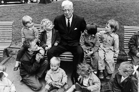 Maurice Pate, first UNICEF Executive Director, sits on a park bench surrounded by children.