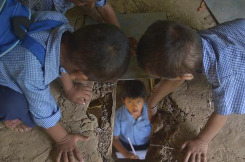 Children look through hole in floor