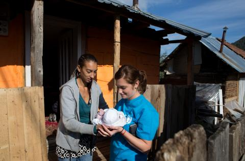 Mother of four Andreea Ursaru (left) and her baby Daria receive a visit from the community nurse
