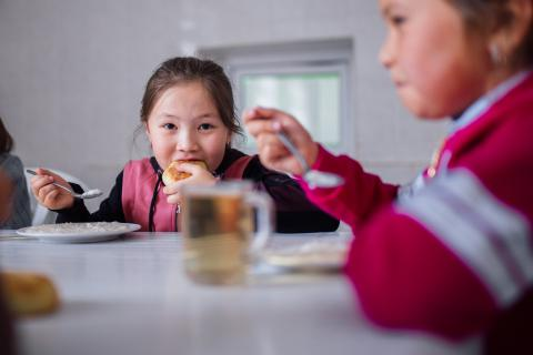 Nurel, 7, a primary school student, eats a healthy lunch prepared by a cook at her school near Chon Kemin valley, Kyrgyzstan, 10 September 2019.