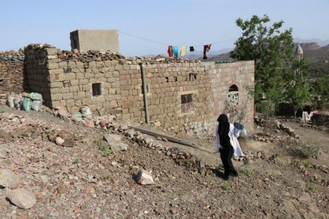 Yemen. A healthcare worker walks to a patient's home.