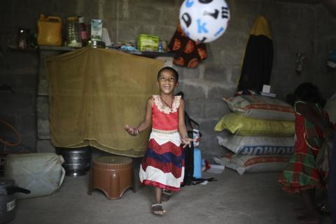 At home in India: A young girl playing with a football inside her home