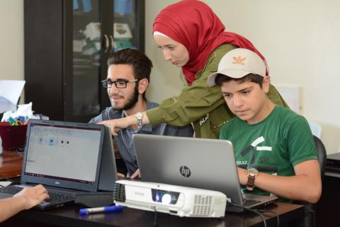 Syria. A woman helps at a technology workshop.