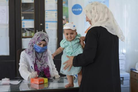 Syria. A woman takes her child for a health check.