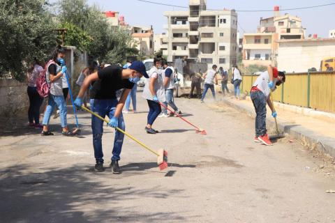 Syria. Young people sweep a street.