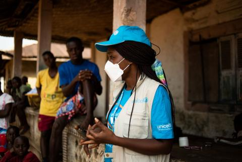 Liberia. A UNICEF health worker talks to people in a village about the polio vaccine.