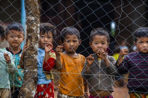 Myanmar. Children look from behind a fence.