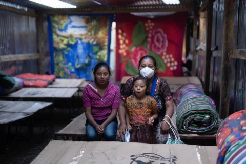 Guatemala. A mother sits on a bed with her children.