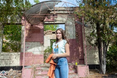Ukraine. A girl stands outside a destroyed building.