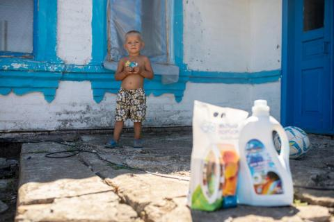 Ukraine. A boy stands outside his home.