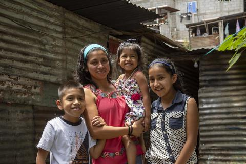 Guatemala. A woman stands with her family.