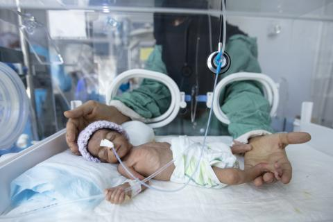 Yemen. A mother reaches out to her baby in an intensive care unit.